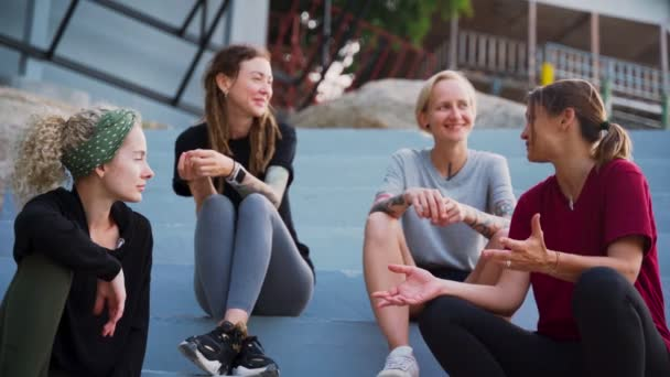 Group of four young women, best friends sitting outdoor and talking.