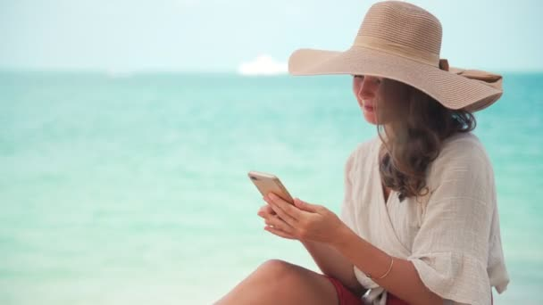A young woman in a big straw hat using her smartphone