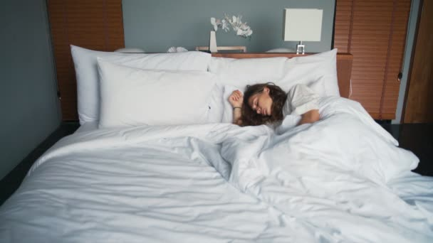 Young caucasian woman sleeping in bed in a hotel room.