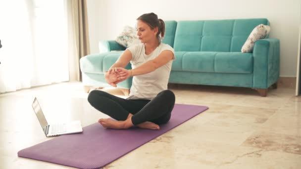 Atraktivní mladá žena dělá jógu strečink jóga on-line doma.