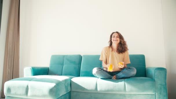 Egy fiatal, gyönyörű nő három naranccsal zsonglőrködik, miközben a kanapén ül.