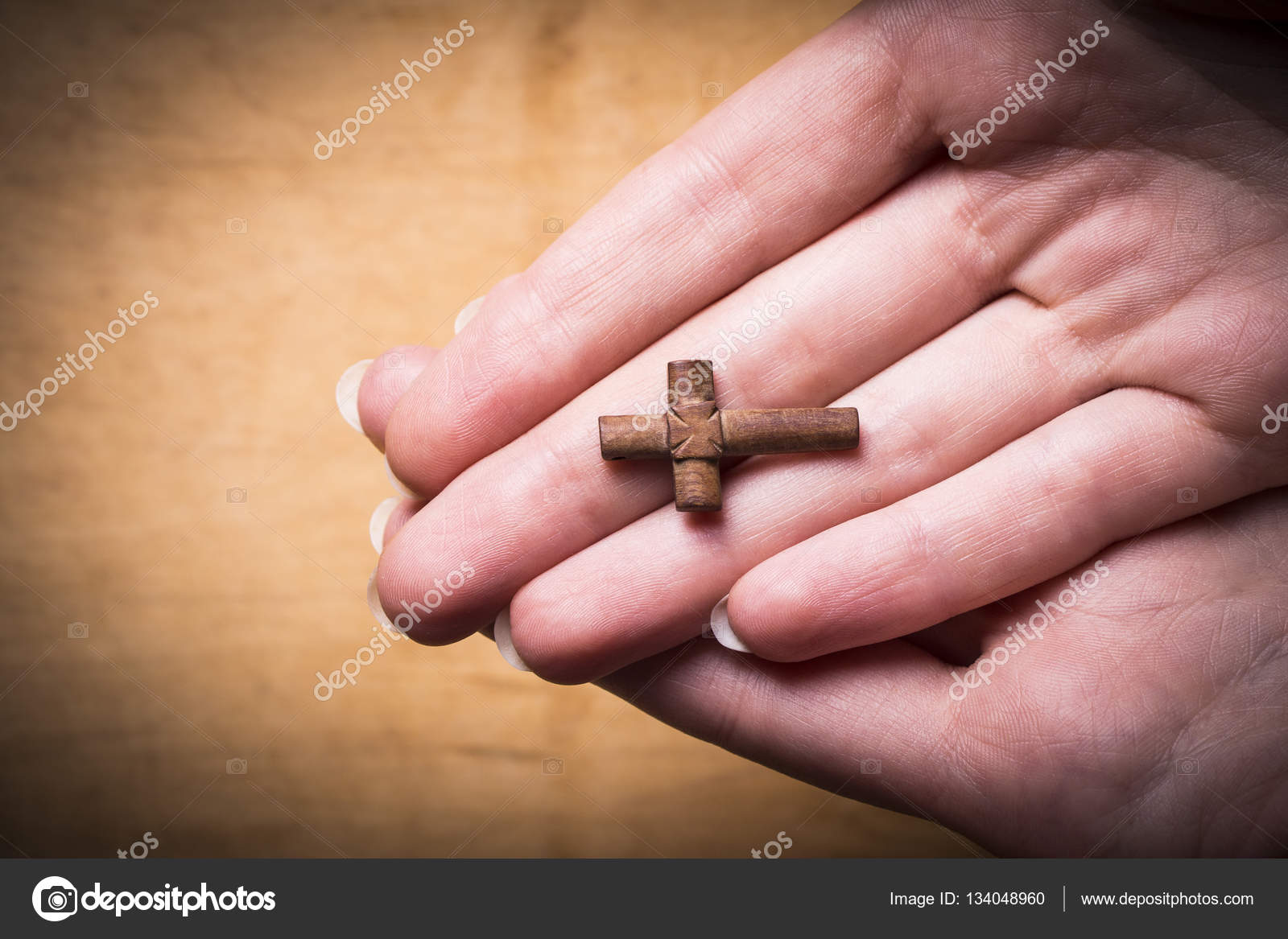 Cross in female hands on a wooden background. — Stock Photo © afta ...