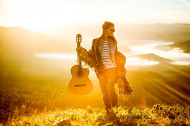 Young girl meets sunrise on top of a mountain with a guitar