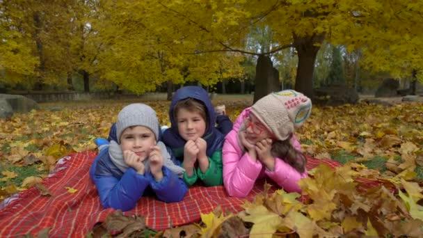 Děti v žluté podzimní parku. Malí chlapci a dívky stojí venku v světlé oblečení
