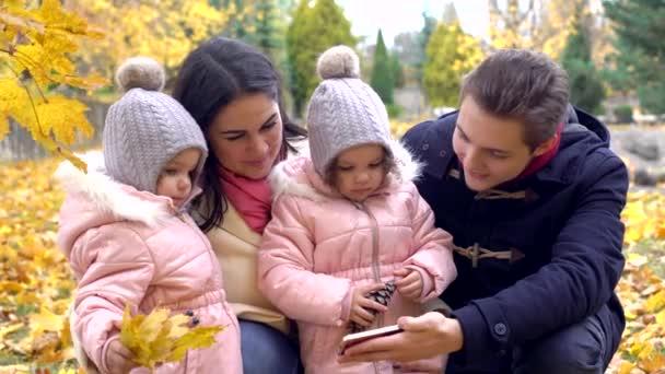 Familie mit zwei Töchtern im Park schaut auf das Telefon in th