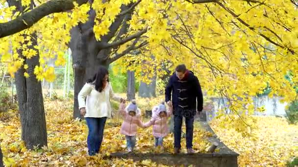 Happy family walking along the alley in the park in autumn. Pare