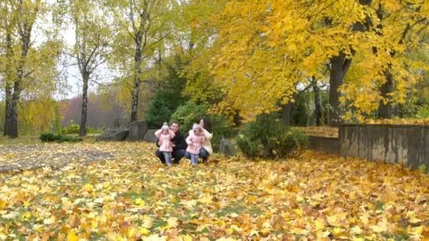 Šťastná rodina hraje v parku se žlutými listy v podzimní pa