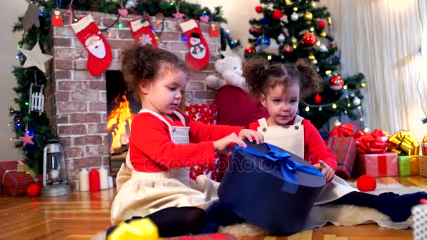 Zwei kleine Mädchen in das Kappen von Santa Claus sitzen auf den Boden-Witz