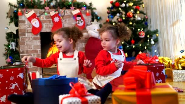 zwei kleine Mädchen in Mützen von Weihnachtsmann auf dem Boden sitzend Witz
