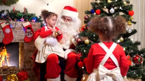 Santa Claus s dítětem zdobí vánoční stromeček v pokoji s vánoční ozdoby