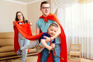 A family dressed in superhero costumes plays  the room