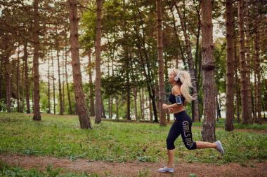 Girl in headphones jogging through the forest