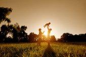 glückliche Familie spielt mit einem Kind bei Sonnenuntergang im Park.