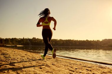 A young woman runner runs at sunset in a park in  the lake.