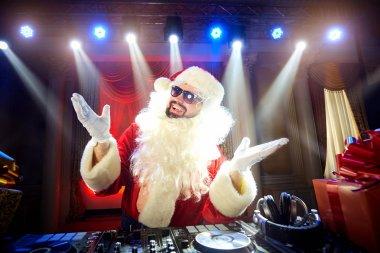 Funny Santa DJ mixes in the beams of light music.