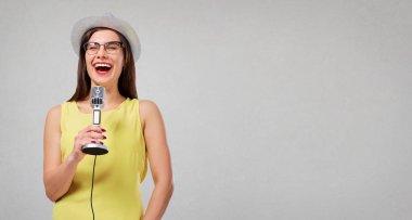 The girl is singing karaoke.