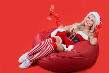 A girl in Santa suit sitting on a Christmas background.