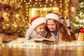 Fotografie Zwei Kinder auf dem Boden lesen Sie ein Buch in einem Raum mit Weihnachten