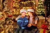 Zwei Kinder mit Geschenken in einem Raum mit Weihnachten.