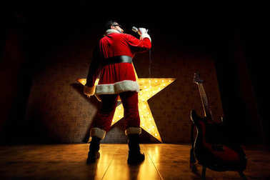 Happy Santa sings into the microphone against the backdrop of a