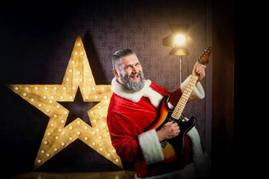 Happy Santa with a guitar is dancing against the background of a
