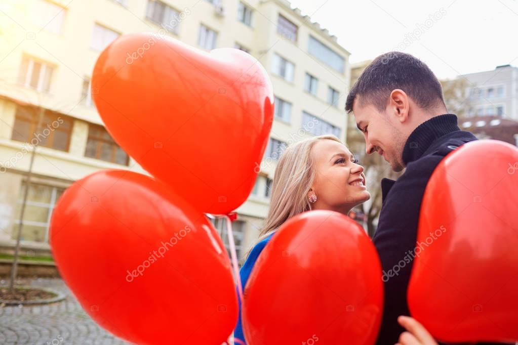 A young couple in a coat are holding a balloons heart in the city street. Valentines Day. stock vector