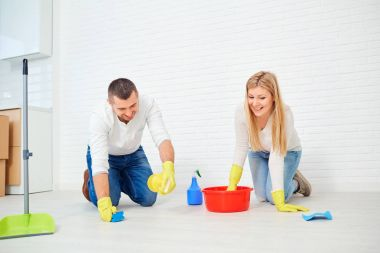 A couple washes the floor.