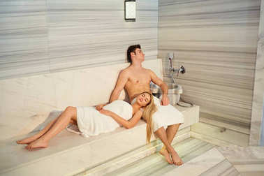 Couple in towels resting in the sauna.