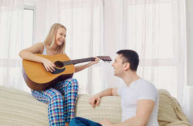 The couple plays the guitar, sings the songs together.