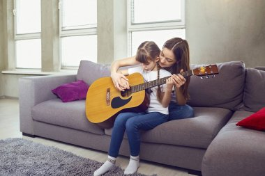 Mom teaches a kid girl to play an acoustic guitar while sitting