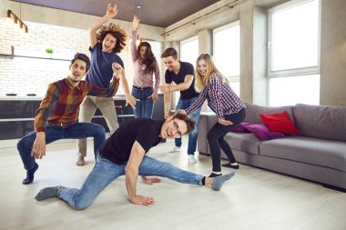 Friends dance at a students party in the apartment.