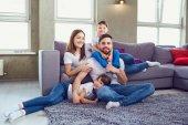 Šťastná rodina s úsměvem, sedí doma