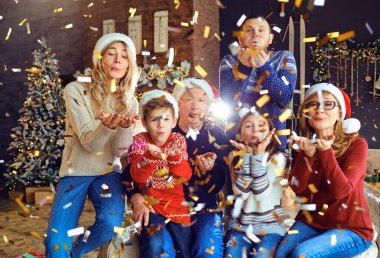 Big happy family blowing confetti at home for Christmas.