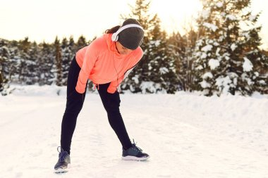 Girl athlete smiling while standing in the park in winter