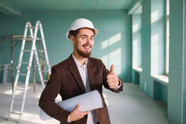 Foreman bearded man in a white helmet in a room at a construction site
