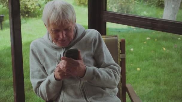 Starší muž šedé vlasy použijte smartphone sedí na verandě v zahradě