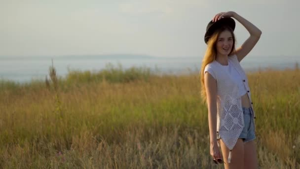 Young beautiful model in hat posing on the edge of a cliff near the river