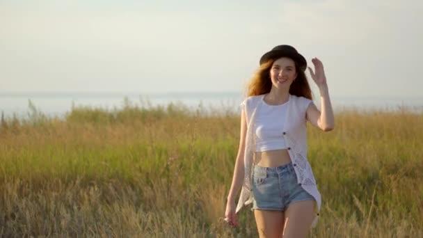 junge schöne Mädchen Modell mit Hut zu Fuß und posiert auf einer Wiese in der Nähe des Flusses