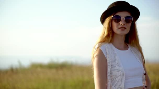 junge schöne Frau Modell mit Hut und Sonnenbrille posiert im Freien Zeitlupe