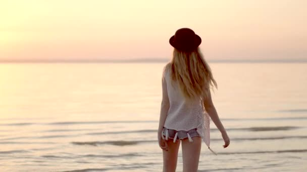 Pretty young blonde girl in hat posing and spinning around herself at sunset