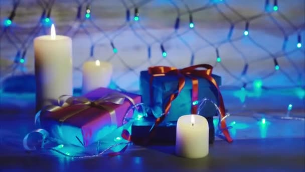 Gift boxes and candles with bright blue garland. Concept christmas and new year