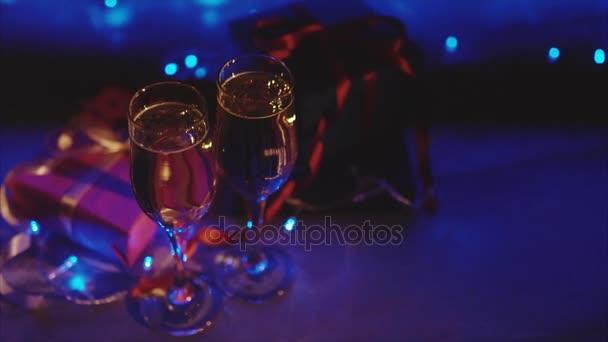 Nahaufnahme von Weihnachts- und Neujahrsgeschenken, zwei Gläser Champagner mit blauem Kranz