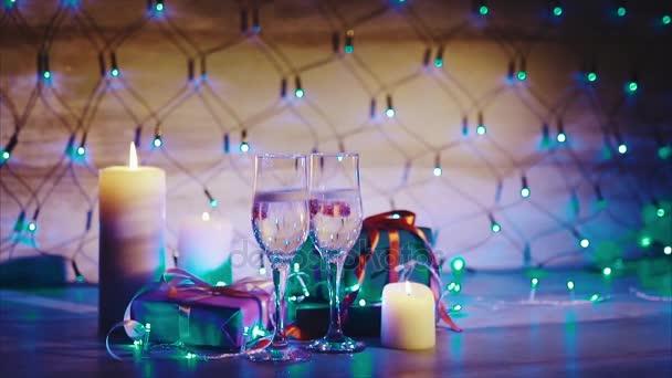 Karácsonyi ajándékokat, gyertyák és két pohár pezsgő kék garland háttér