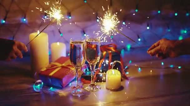 Hände mit Wunderkerzen auf dem Hintergrund von Weihnachten Geschenke, Kerzen und Champagner