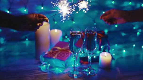 Ruce s prskavky, svíčky, dárky a šampaňské. Oslava Vánoc