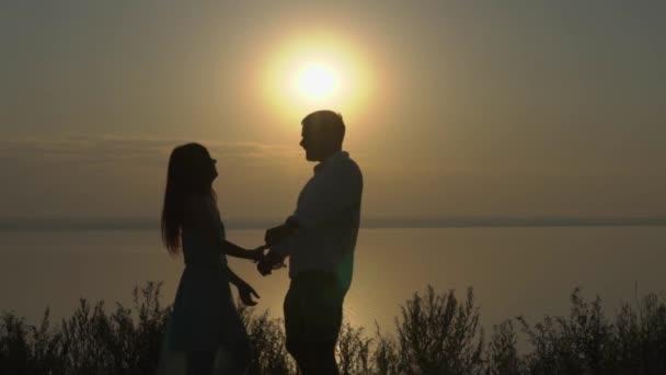 Šťastný mladý pár objímání a líbání u moře na západ slunce. Pojetí lásky