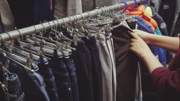 Frau sucht sich im Second-Hand-Laden eine Hose für den Jungen aus