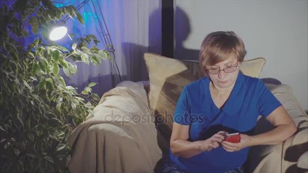 Starší žena doma pomocí chytrého telefonu sedí na křesle
