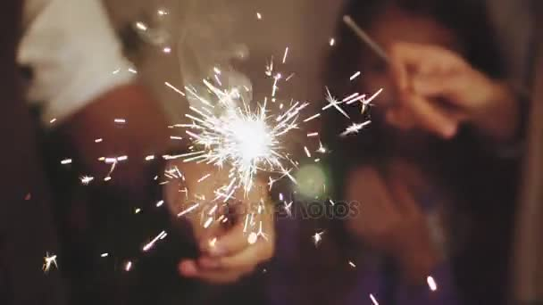 Close up family hands with sparklers lights in christmas eve