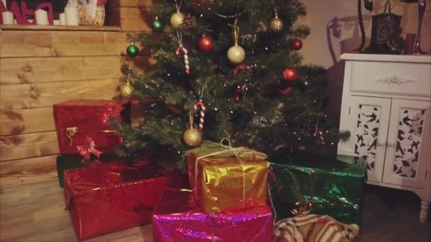 Dary a dárky pod vánoční stromeček ve vyzdobeném pokoji
